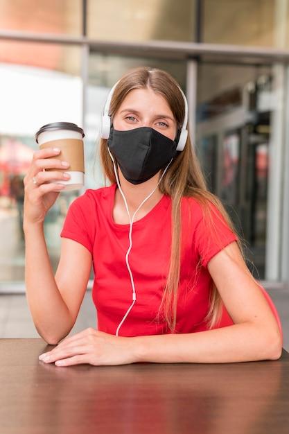 Donna del ritratto al terrazzo con la maschera Foto Gratuite
