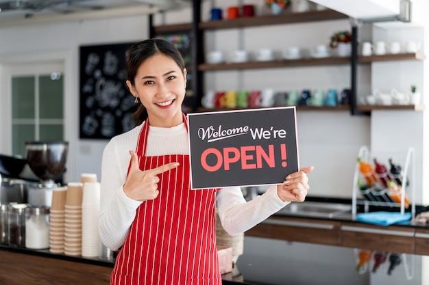Portrait of woman waitress standing at her coffee shop gate with showing open signboard Premium Photo