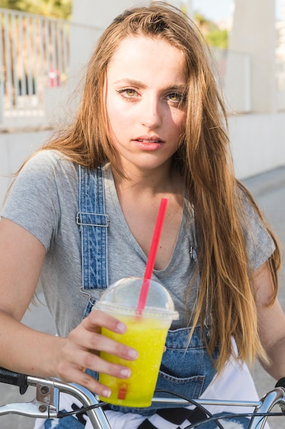 Portrait of a woman with bicycle holding glass of juice Free Photo