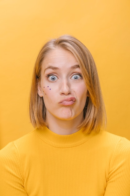 Portrait of woman with different facial expressions in a yellow scene Free Photo