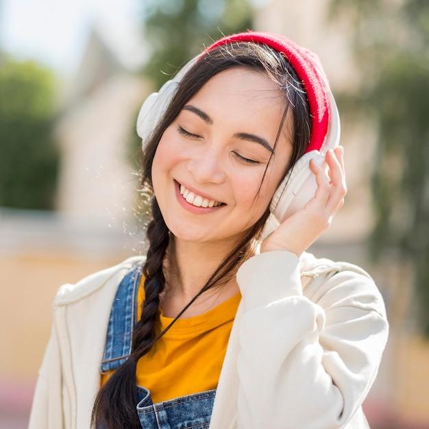 Женщина портрета с наушниками слушая музыка Premium Фотографии