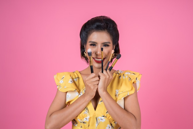 Portrait of woman with makeup brush professional show Free Photo