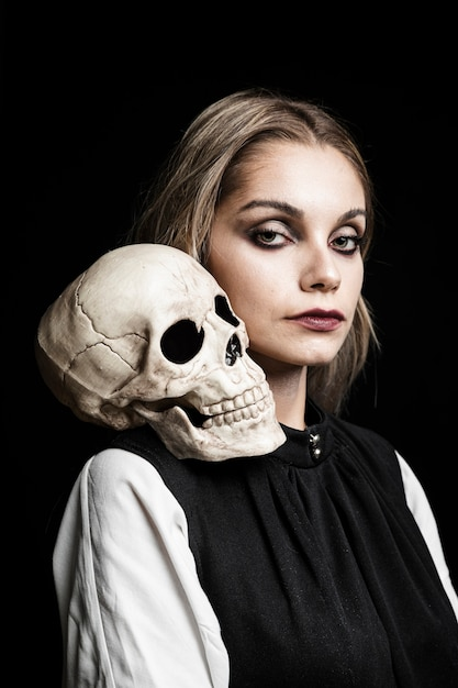 Portrait of woman with skull on shoulder Free Photo