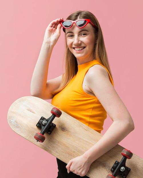 Портрет женщины с солнцезащитными очками и скейтбордом Бесплатные Фотографии