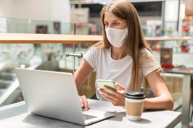 Donna del ritratto che lavora al computer portatile con la maschera Foto Gratuite