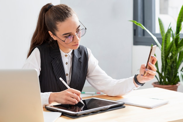 Portrait of woman working with multiple devices Free Photo