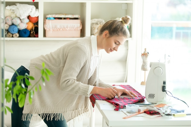 Portrait of a woman working with a sewing pattern Free Photo