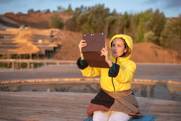 Portrait of a woman in a yellow jacket with a blanket on a wooden pier, photographed on a tablet sunrise Premium Photo