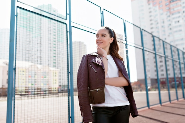 Ritratto di meravigliosa modella bianca con trucco luminoso che esprime energia in buona giornata nella metropoli Foto Gratuite