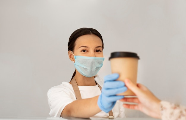 Ritratto di lavoratore con maschera e guanti chirurgici Foto Gratuite