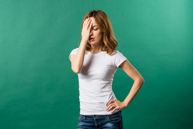 Portrait of worried young woman against green background Free Photo