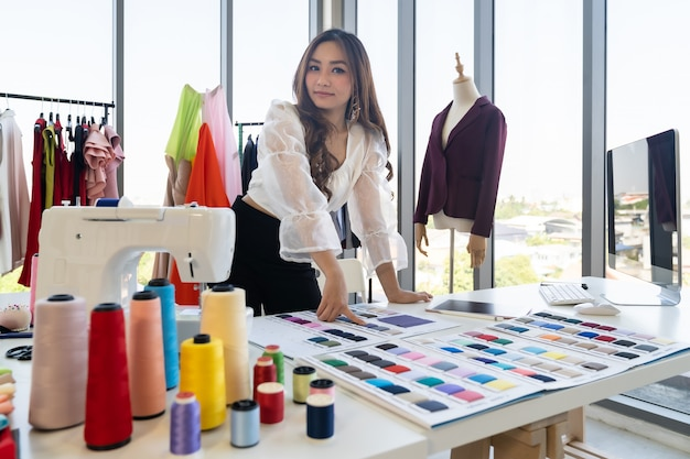Portrait of young adult asian fashion designer working from home with colour palette as owner entrepreneur at her atelier studio. using for entrepreneur small business startup concept. Premium Photo