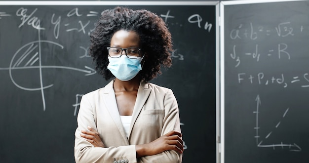 Portrait of young african american female teacher in glasses and medical mask looking at camera and crossing hands in classroom. blackboard with math formulas on background. pandemic schooling. Premium Photo