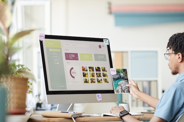 Portrait of young african-american photographer managing photo stock marketplace while using computer at desk in home office with photo website on screen, copy space Premium Photo