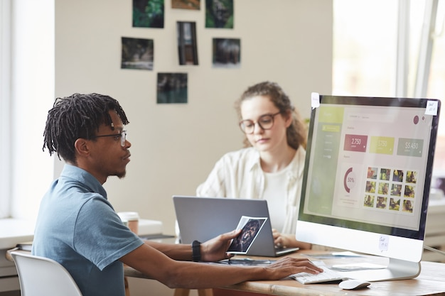 Portrait of young african-american photographer managing photo stock marketplace while using computer at desk in office with website on screen, copy space Premium Photo