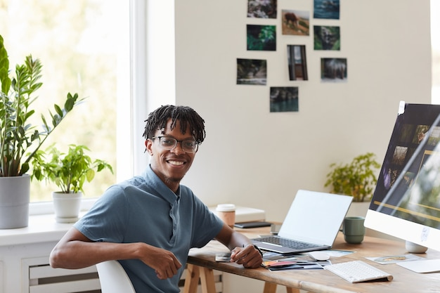 Portrait of young african-american photographer smiling at camera while posing at desk with photo editing software on computer screen, copy space Premium Photo