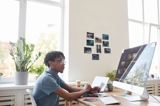 Portrait of young african-american photographer using computer at desk in home office with photo editing software on screen, copy space Premium Photo