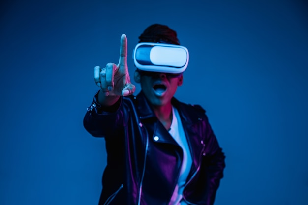 Portrait of young african-american woman's playing in vr-glasses in neon light on blue background Free Photo