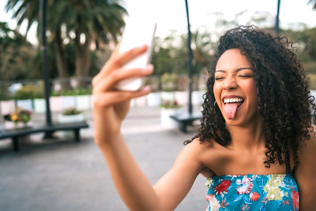 Portrait of young afro american latin woman taking a selfie with mobile phone outdoors in the street. Free Photo
