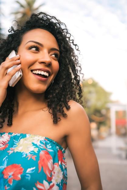 Ritratto di giovane donna latina afro-americana, parlando al telefono all'aperto in strada. concetto di tecnologia. Foto Gratuite