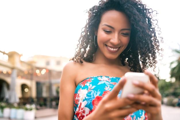 Ritratto di giovane donna latina afroamericana utilizzando il suo telefono cellulare all'aperto in strada. concetto di tecnologia. Foto Gratuite