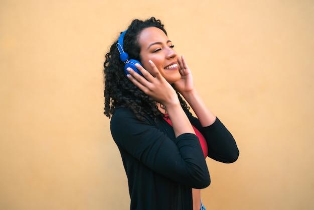 Ritratto di giovane donna afro che gode e ascolta la musica con le cuffie blu. concetto di tecnologia e stile di vita. Foto Gratuite