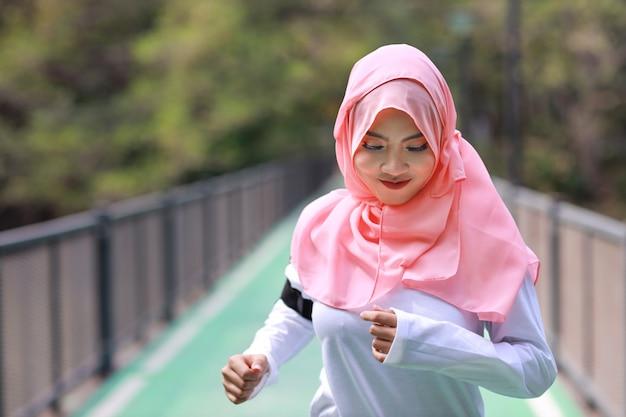 マラソントレーニングのために屋外ジョギングスポーツウェアの肖像若い、美しいアジアのイスラム教徒の女性。緑の木の背景を持つ屋外のコンクリートの道に沿って運動かわいいジョガーガール。スポーツコンセプト Premium写真