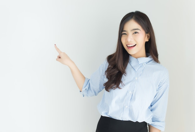 Portrait of young asian business woman pointing up over white background. Premium Photo