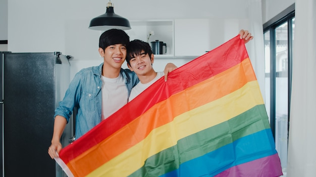 Portrait young asian gay couple feeling happy showing rainbow flag at home. asia lgbtq+ men relax toothy smile looking to camera while hug in modern kitchen at house in the morning . Free Photo