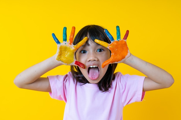 Portrait of young asian girl with art, thai funny kid show water color on palm and creativity  of children concept Premium Photo
