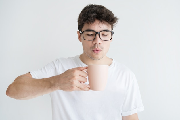 Portrait of young asian man blowing at hot coffee in cup Free Photo