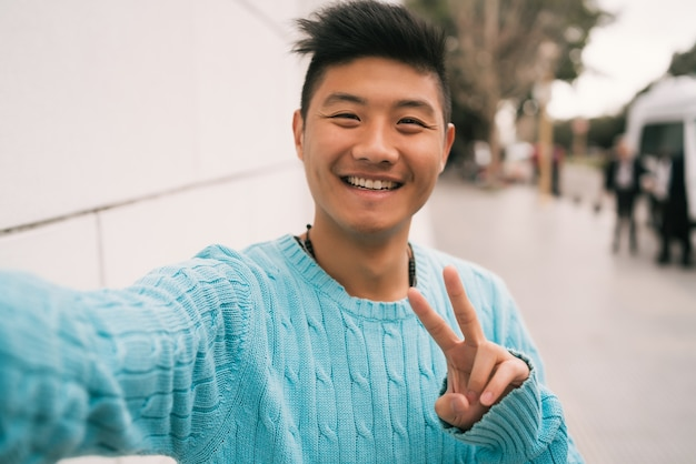 Portrait of young asian man looking confident and taking a selfie while standing outdoors in the street. Free Photo