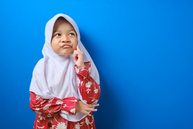 Portrait of young asian muslim girl looked happy, thinking and looking up, having good idea. half body portrait against blue background with copy space Premium Photo