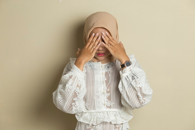Portrait of young asian muslim woman wearing hijab covers her face with her hands Premium Photo