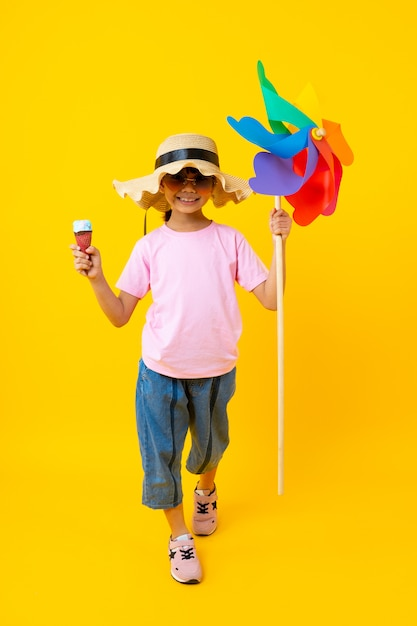 Portrait of young asian pretty girl walking and  holding colorful turbine and ice cream,thai kid in summer style Premium Photo
