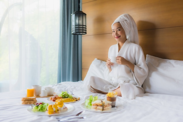 Portrait young asian woman on bed with breakfast in bedroom Free Photo