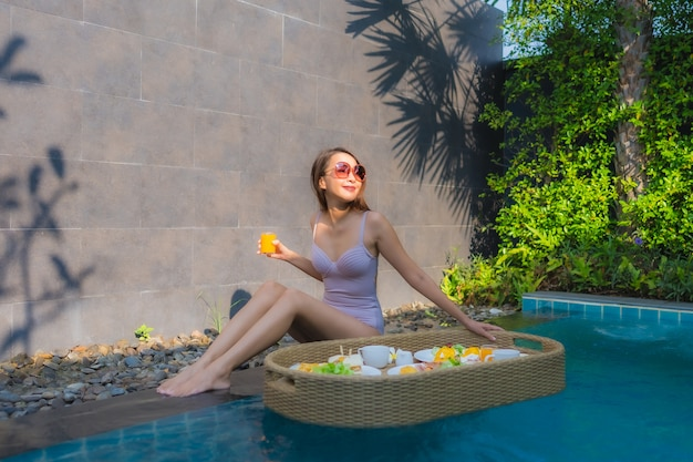 Portrait young asian woman happy smile enjoy with floating breakfast tray in swimming pool in hotel Free Photo