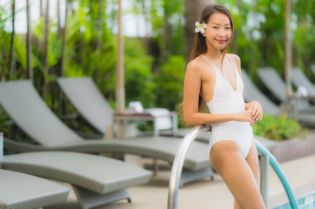 Portrait young asian woman happy smile relax around swimming pool in hotel resort Free Photo