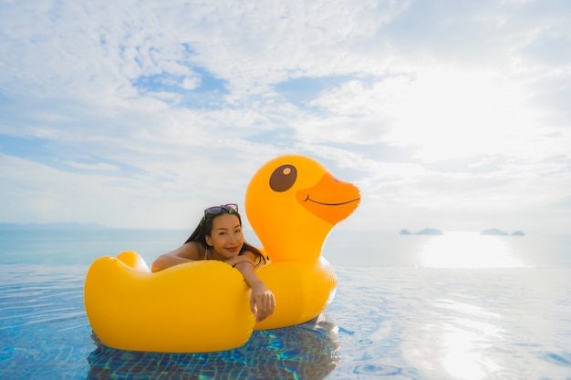 Portrait young asian woman on inflatable float yellow duck around outdoor swimming pool in hotel and resort Free Photo