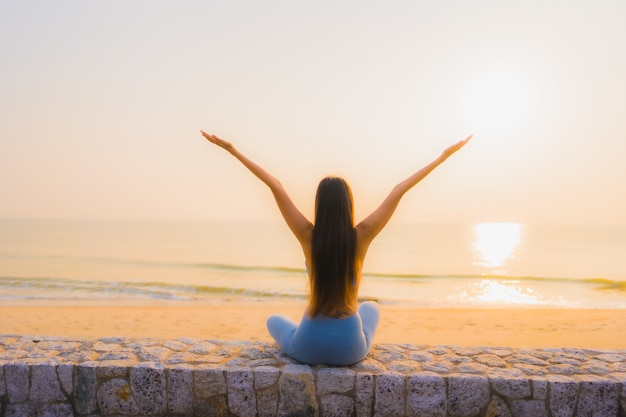 Portrait young asian woman do meditation around sea beach ocean at sunrise Free Photo