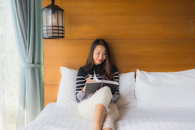 Portrait young asian woman read book in bedroom Free Photo