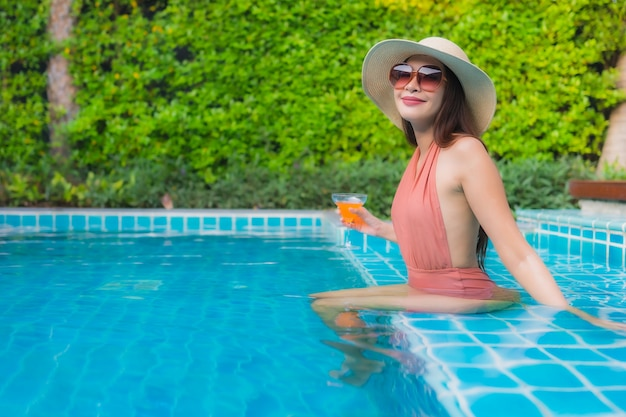 Portrait young asian woman relax happy smile around swimming pool in hotel Free Photo