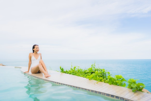 Portrait young asian woman relax smile happy around outdoor swimming pool in hotel resort with sea ocean view Free Photo