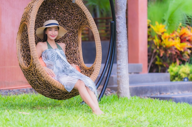 Portrait young asian woman sitting on swing chair in the garden Free Photo