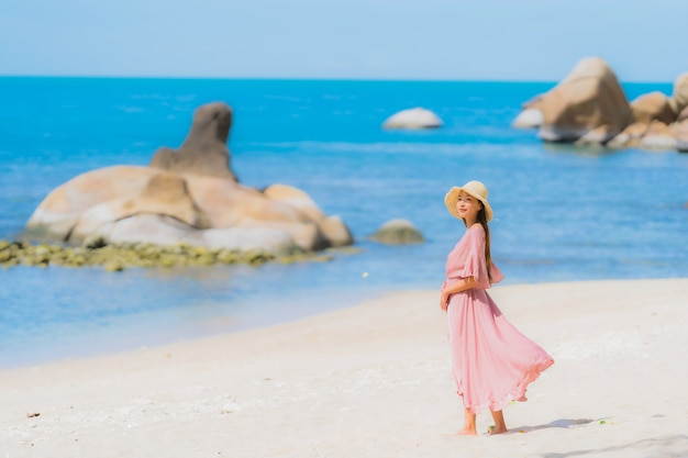 Portrait young asian woman smile happy around beach sea ocean with coconut palm tree for holiday vacation Free Photo