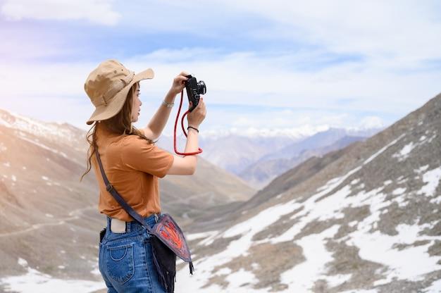 Portrait of young asian woman taking photos on snow mountain Premium Photo