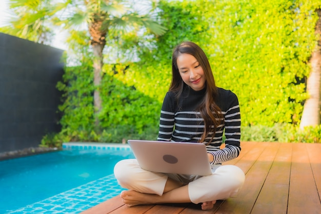 Portrait young asian woman using laptop computer around outdoor swimming pool Free Photo