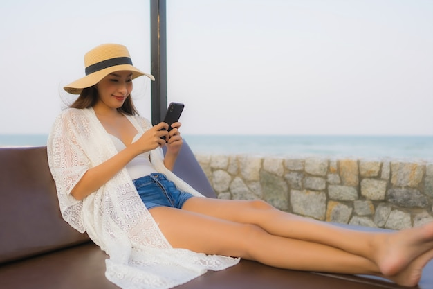 Portrait young asian woman using smart mobile phone around outdoor beach sea Free Photo