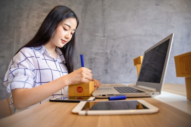 Portrait of young asian working online shopping with laptop computer at home. selling online and delivery concept Premium Photo