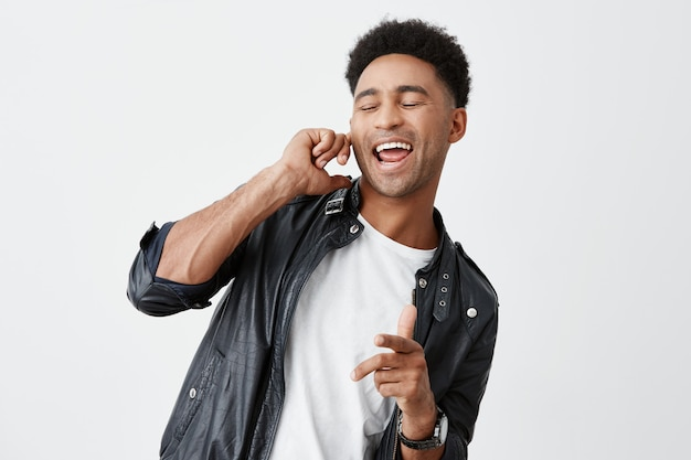 Portrait of young attractive black-skinned american male student with curly hair in white t-shirt and leather jacket closing eyes, holding finger near ear, singing loudly on party. Free Photo